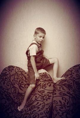 мальчик забрался на спинку кресла