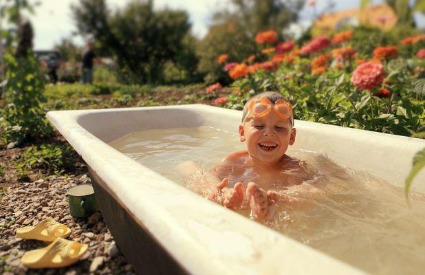 мальчик купается в старой ванне